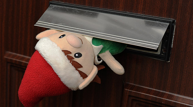 Santa's Elf squeezing out of the letter box